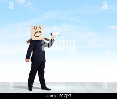 Businessman with box on head screaming in megaphone - Stockfoto