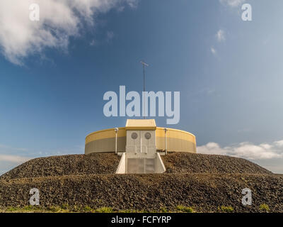 Circular industrial yellow and gray building on top of gravel platform against a blue sky with clouds near Keflavik - Stock Photo