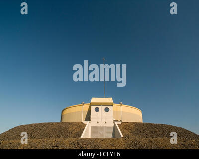 Circular industrial yellow and gray building on top of gravel platform against a blue clear sky near Keflavik Iceland. - Stock Photo