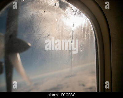 Spinning propeller grid of land, clouds and blue sky seen through aeroplane window with condensation and dripping - Stock Photo