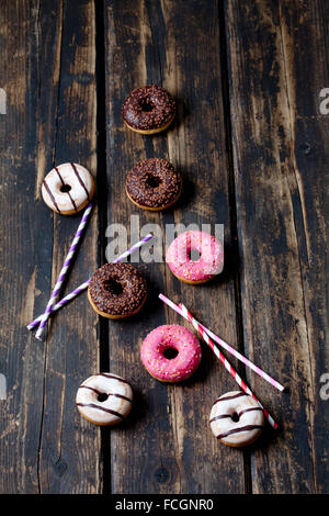 Drinking straws and doughnuts   different icings on dark wood - Stockfoto