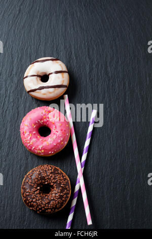 Three doughnuts   different icings and two drinking straws on slate - Stockfoto