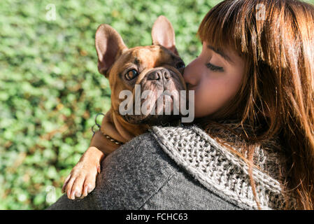 Portrait of young woman kissing French bulldog - Stock Photo