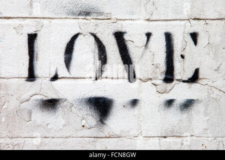 LONDON, UK - JANUARY 13TH 2016: The word LOVE sprayed onto a brick wall in London, on 13th January 2016. - Stock Photo