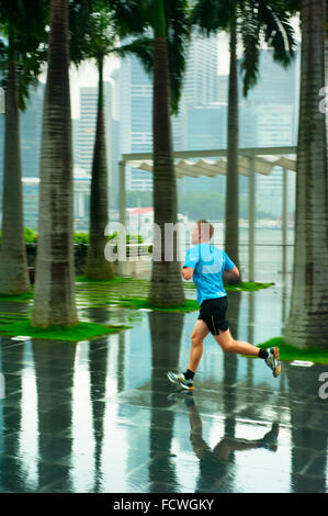 Unidentified man running in front of Singapore downtown in the rain. Singapore has been recognized - Stock Photo