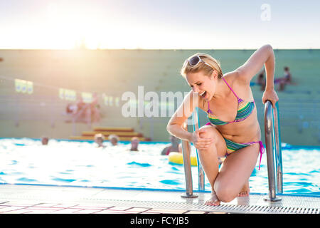 Young woman with injured leg - Stock Photo