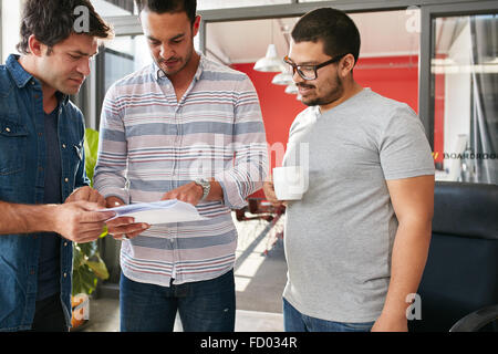 Group of young creative professionals having a meeting in office, going through some documents together. Creative - Stock Photo