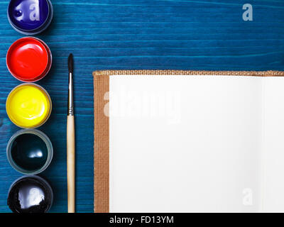 Brush and paint for painting. Liquid paint on a background of blue wooden surface - Stock Photo