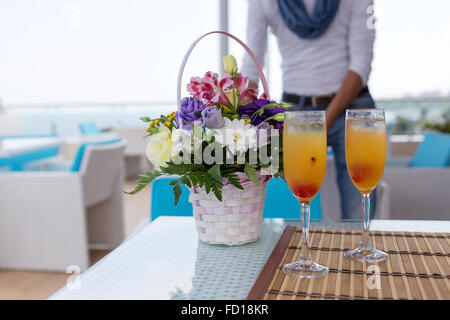 Alcoholic drink with fruit juice in glass. Blur beautiful bouquet of flowers. Soft selective focus. - Stock Photo