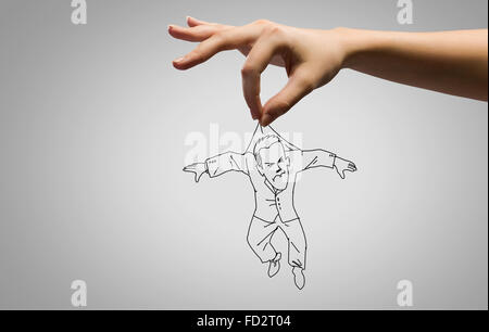 Close up of human hand catching running away businessman - Stock Photo