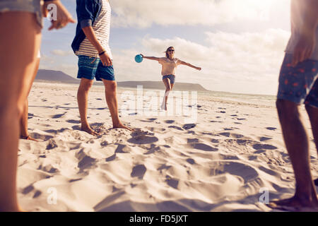 Low angle shot of young woman running on the beach with a ball with her friends standing in front. Group of friends - Stock Photo