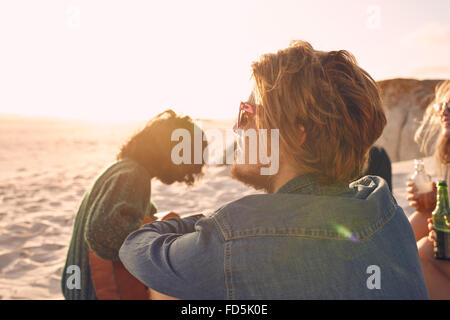 Young man enjoying a summer day at the beach with group of friends in background. Young people enjoying a day on - Stock Photo