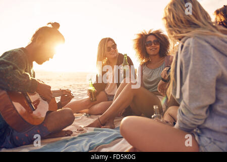 Group of young people sitting at the beach together while young man playing guitar. Group of friends partying on - Stock Photo