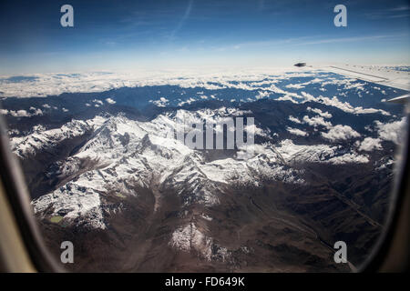 View Of Snowy Mountain Range From Airplane Window - Stock Photo