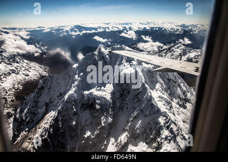 View Of Snowy Mountain From Airplane Window - Stock Photo