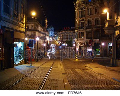 Cobblestone Street Along Buildings At Night - Stock Photo