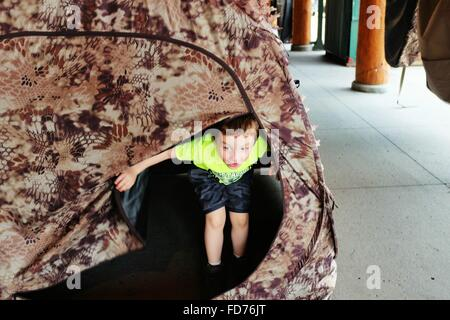 Little Boy Peeking Out From Tent - Stock Photo