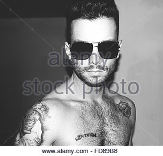 Portrait Of Shirtless Man Wearing Sunglasses At Home - Stock Photo