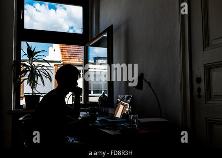 Silhouette Of Man Using Laptop At Desk - Stock Photo