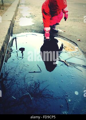 Girl Putting Hand Into Puddle - Stock Photo