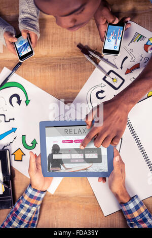 Composite image of overhead view of creative team working at desk - Stock Photo