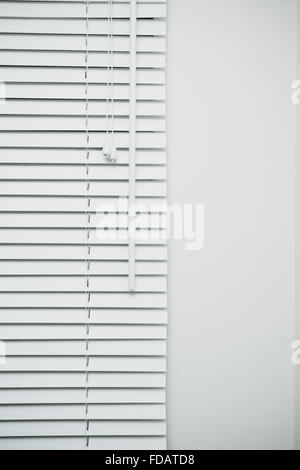 Part of a blind covering a window in a room - Stock Photo