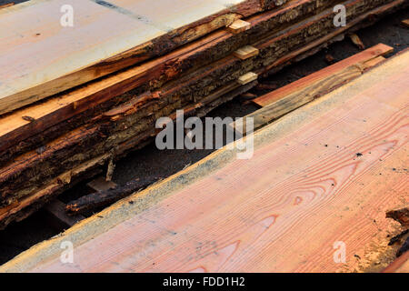 Wood planks stickered and stacked for seasoning outdoors - Stock Photo