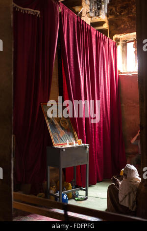 Red curtains catch the low light inside a stone-cut church near Mekele in Ethiopia - Stock Photo