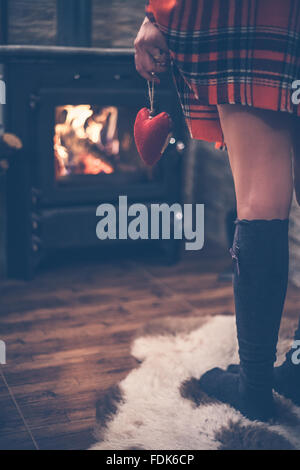 Rear view of a woman standing in front of wood burning stove holding red heart in her hand - Stock Photo