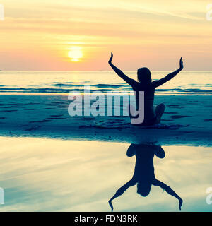 Silhouette of a young woman sitting on the beach during a beautiful sunset, with reflection in the water. Serenity, - Stock Photo