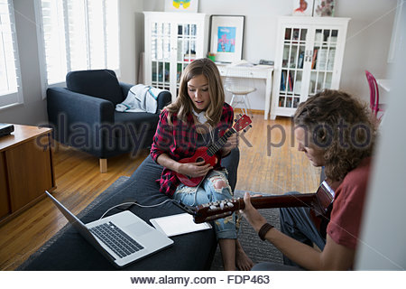 Couple playing guitar and ukulele in living room - Stock Photo