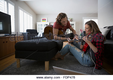 Couple with digital tablet playing guitar and ukulele - Stock Photo