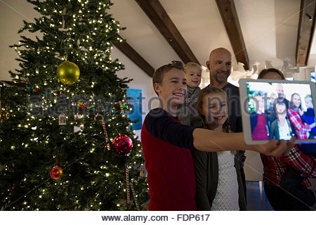 Family taking selfie with digital tablet Christmas tree - Stockfoto