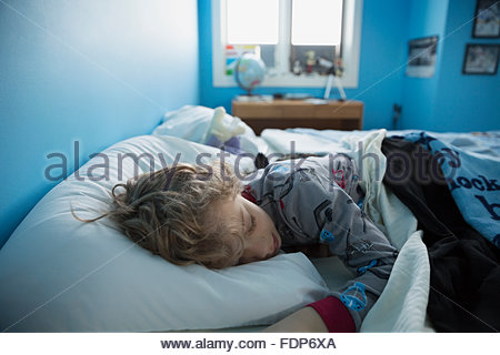Boy sleeping in bed - Stock Photo