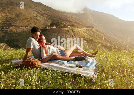 Happy young couple on picnic blanket. They are relaxing together on a summer day. - Stockfoto