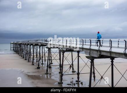 Mature runner in heavy rain on Saltburn`s Victorian pier. Saltburn by the Sea, North Yorkshire - Stock Photo