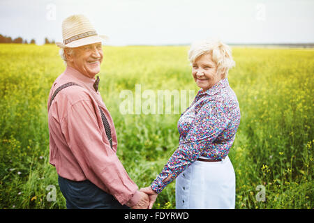 Affectionate seniors holding by hands while standing in meadow - Stock Photo