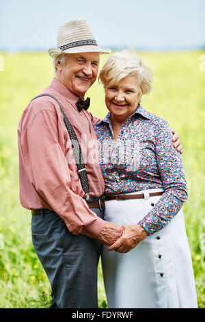 Affectionate seniors holding by hands in rural environment - Stock Photo