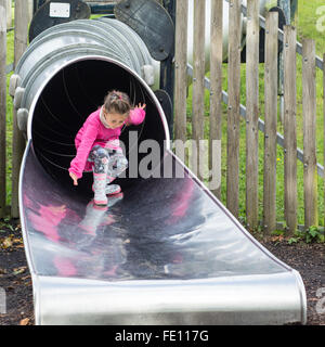 Young girl emerging from big slide. A small child strikes a pose after sliding down a long metal tube in a playground - Stock Photo