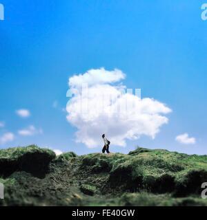Man Walking On Mountain Against Sky - Stock Photo