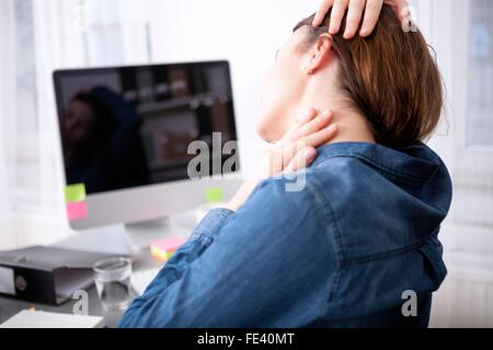 Close up rear View Tired Office Woman Sitting at her Desk Massaging her Neck While Holding her Head. - Stockfoto
