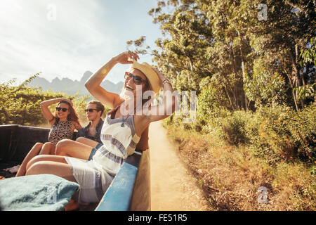 Portrait of a cheerful young woman sitting in the back of pickup truck with friends. Young people enjoying on a - Stock Photo