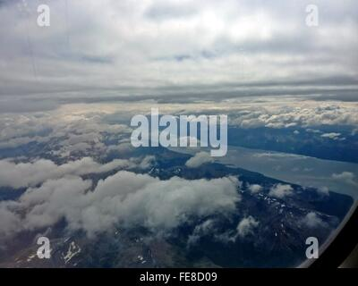 Clouds Over Dramatic Landscape Seen Through Airplane Window - Stock Photo