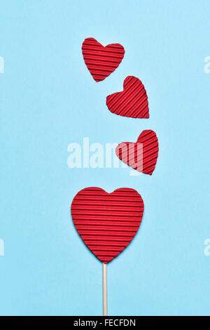 some hearts made with red corrugated paperboard, one of them stacked in a stick like a lollipop, against a blue - Stock Photo
