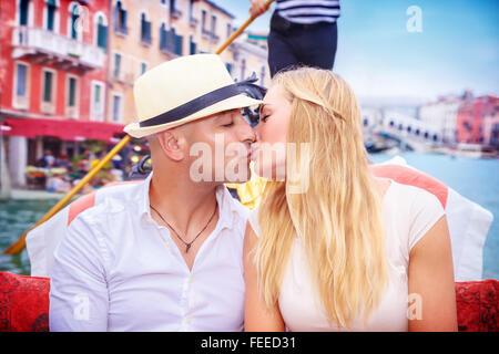 Portrait of happy loving couple in romantic honeymoon, kissing on a gondola, vacation in Italy, enjoying holidays - Stock Photo