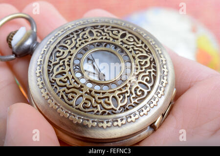 Man holding a retro styled Pocket watch in hand - Stock Photo