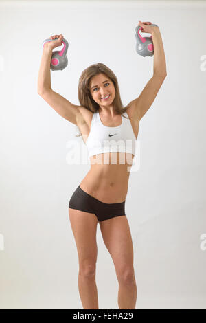 Young woman with slim body holding up kettle bells and looking happy - Stock Photo