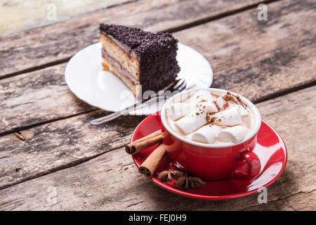 Hot cocoa with marshmallows and slice of chocolate cake on wooden background. Close up image of hot beverage with - Stock Photo
