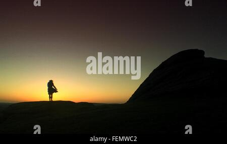 Silhouette Of Woman Standing On Rocks - Stock Photo