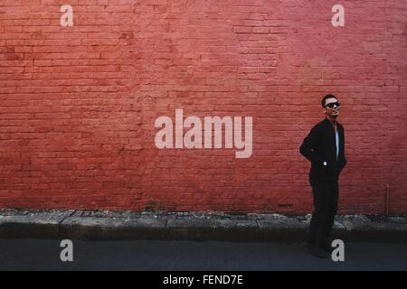Smiling Young Man In Sunglasses Standing On Footpath - Stock Photo